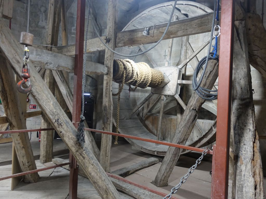 the big wheel was used to take building material to the top of the church to build the huge spire that was added (and added enough weight to almost collapse the entire church)