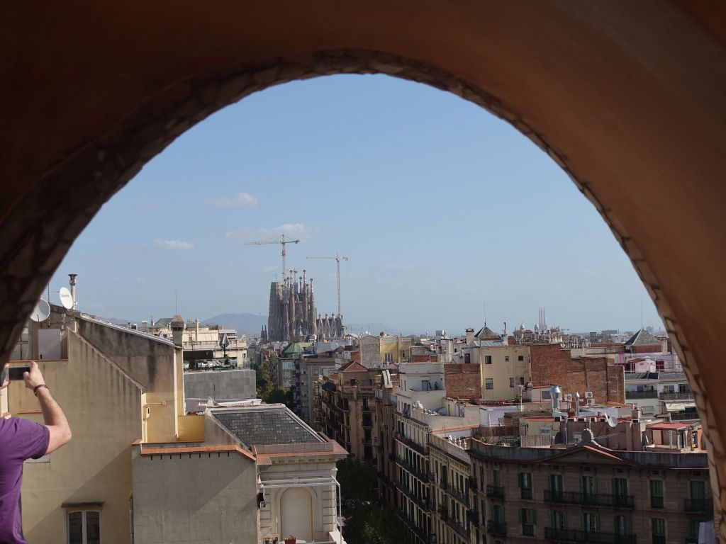 one of the building's arches has a view on the unfinished Sagrada Familia