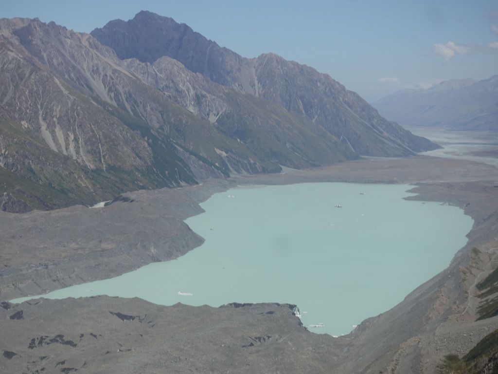 this is the edge of the glacier that melts into a lake, with a few visible icebergs